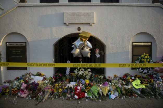 A morning view of a memorial outside the Emanuel AME Church June 19, 2015 in Charleston, South Carolina. US police arrested a white high school dropout Thursday suspected of carrying out a gun massacre at one of America's oldest black churches, the latest deadly assault to fuel simmering racial tensions. Authorities detained 21-year-old Dylann Roof, shown wearing the flags of defunct white supremacist regimes in pictures taken from social media, after nine churchgoers were shot dead during a Bible study class on Wednesday evening. AFP PHOTO/BRENDAN SMIALOWSKI        (Photo credit should read BRENDAN SMIALOWSKI/AFP/Getty Images)